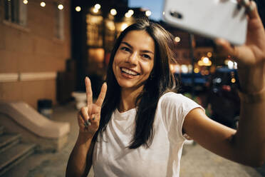 Young woman using smartphone in the city at night, taking a selfie - OYF00081