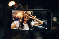 Young woman using smartphone in the city at night, taking a selfie - OYF00084