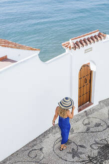 Back view of woman wearing blue dress and straw hat walking along alley, Nerja, Spain - LJF00990