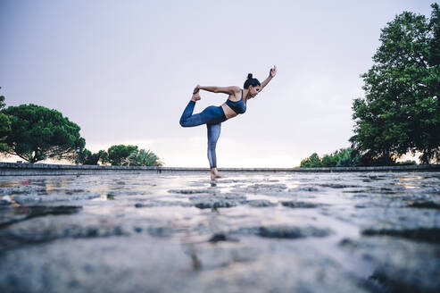 Woman practicing yoga in the rain, dancer position - OCMF00738