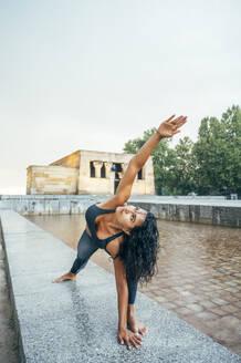 Woman practicing yoga in the rain - OCMF00741