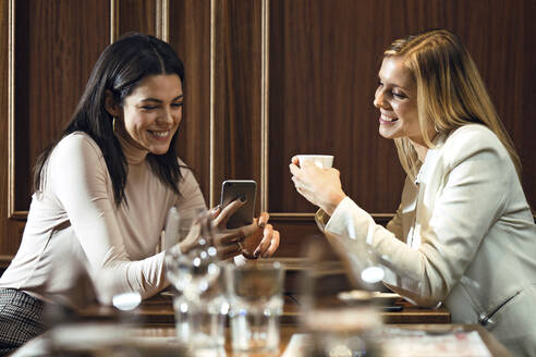 Two happy women in a restaurant looking at smartphone together - JSRF00606