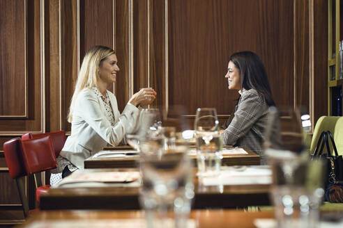 Shot of two pretty young business women talking together while eating in a restaurant. - JSRF00609