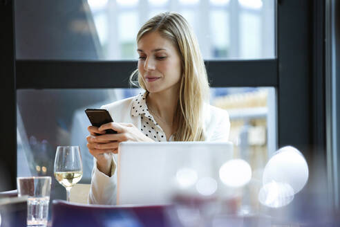 Businesswoman using cell phone in a restaurant - JSRF00618