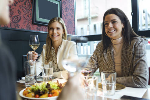 Shot of three pretty young business women talking while eating together in a restaurant. - JSRF00624