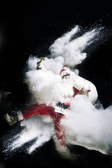 Santa Claus with exploding snow bomb against black background - OCMF00752