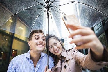 Happy couple with umbrella taking a selfie in Ginza, Tokyo, Japan - MCVF00025