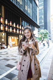 Happy young woman holding takeaway drink and using smartphone in Ginza, Tokyo, Japan - MCVF00028
