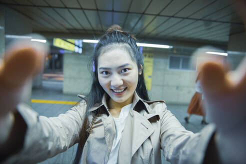 Selfie portrait of smiling young woman at Ginza underground station, Tokyo, Japan - MCVF00037