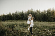 Young couple on a meadow, woman jumping - LHPF00858