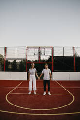 Young couple on a basketball ground, holding hands - LHPF00882