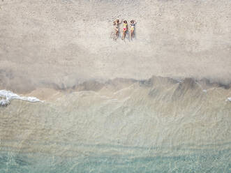 Aerial view of young women lying at the beach, Gili Air island, Bali, Indonesia - KNTF03448