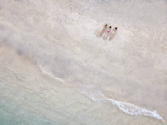 Aerial view of young women lying at the beach, Gili Air island, Bali, Indonesia - KNTF03451