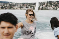 Happy woman with friends on a boat trip on a lake - LHPF00885