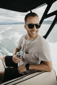 Happy man wearing sunglasses on a boat trip on a lake - LHPF00906