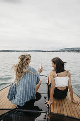 Happy female friends on a boat trip on a lake - LHPF00927