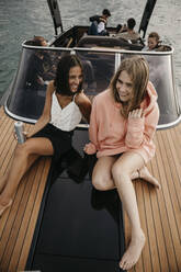 Happy friends on a boat trip on a lake - LHPF00930