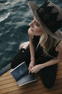 Woman with a book on a boat - LHPF00933