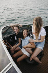 Happy female friends having fun on a boat trip on a lake - LHPF00951