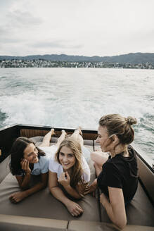 Happy female friends on a boat trip on a lake - LHPF00954