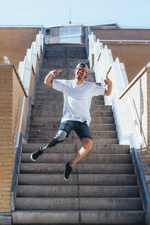 Happy young man with leg prosthesis jumping on stairs inb the city - JCMF00221