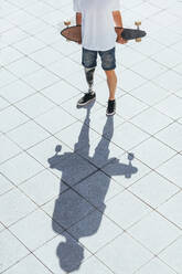 Young man with leg prosthesis holding skateboard - JCMF00224