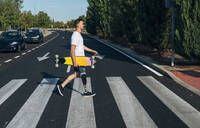 Young man with leg prosthesis holding skateboard and walking on crosswalk - JCMF00227