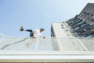 Young man with leg prosthesis performing parkour in the city - JCMF00233