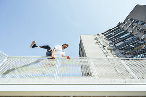 Young male with leg prosthesis performing parkour on building terrace - JCMF00233