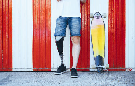 Young man with leg prosthesis standing next to skateboard at  a wall - JCMF00236