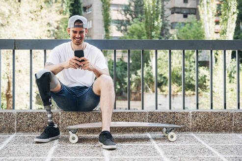 Smiling young man with leg prosthesis and skateboard using smartphone - JCMF00239