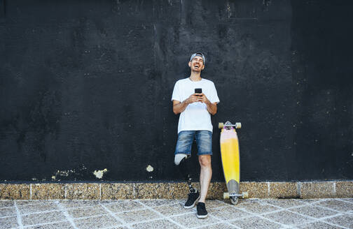 Laughing young man with leg prosthesis and skateboard using smartphone - JCMF00242