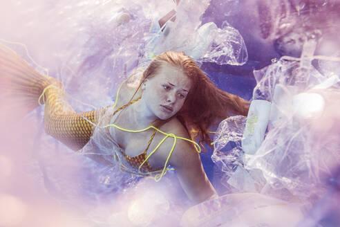Teenage mermaid girl surrounded by plastic waste under water - STBF00401