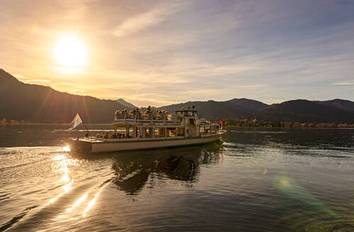 People traveling in ferry on Lake Tegernsee against sky during sunset, Bavaria, Germany - LH00716
