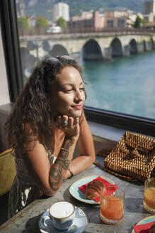 Portrait of smiling young woman sitting at breakfast table in a coffee shop, Lecco, Italy - MCVF00042