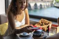 Young woman paying bill with smartphone at coffee shop - MCVF00045