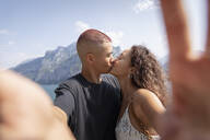 Young couple taking selfie while kissing, Lecco, Italy - MCVF00048