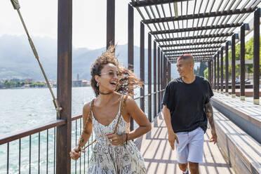 Happy young couple on lakeside promenade, Lecco, Italy - MCVF00054