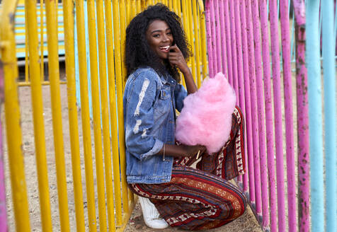 Portrait of happy young woman with pink candyfloss at fair - VEGF00732