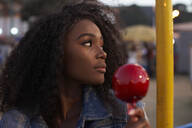 Portrait of young woman candied apple at fair in the evening - VEGF00738