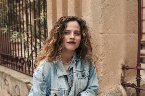 Beautiful teenager with blonde curly hair and blue eyes wearing a blue denim jacket. Palma de Mallorca, Balearic Islands, Spain. - LOTF00075
