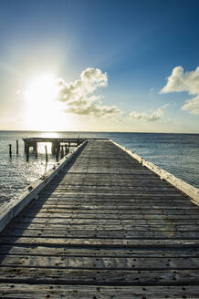 Diminishing perspective of pier over sea against sky at sunset, Cockburn town, Grand Turk - RUNF03228