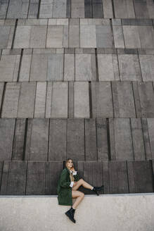 Blond young woman wearing green jacket sitting on a wall, Vienna, Austria - LHPF00958