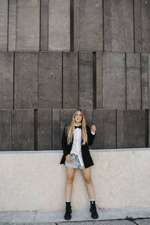 Portrait of blond young woman wearing black tie, blazer and jeans shorts, Vienna, Austria - LHPF00961