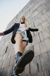 Young woman balancing on one leg, MuseumsQuartier, Vienna, Austria - LHPF00964