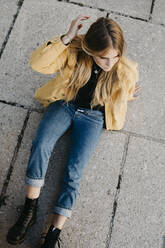 Young woman wearing yellow jacket sitting on the ground - LHPF00970