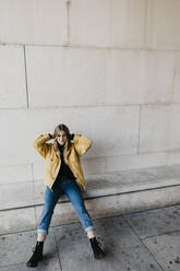 Portrait of young woman wearing jeans and yellow jacket sitting on a wall - LHPF00973