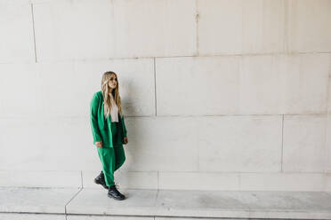 Blond young woman wearing green pantsuit outdoors - LHPF00976