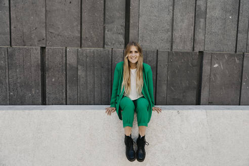 Blond young woman wearing green pantsuit sitting on a wall, Vienna, Austria - LHPF00979