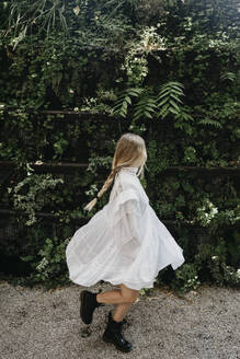 Blond young woman wearing white summerdress dancing outdoors - LHPF00985